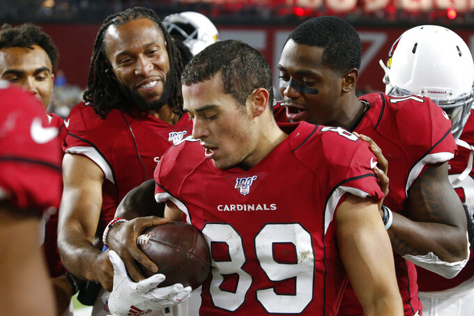 Arizona Cardinals wide receiver Larry Fitzgerald hands the football to wide receiver Andy Isabella (89) after Isabella scored a touchdown against the Oakland Raiders during the second half of an an NFL preseason football game, Thursday, Aug. 15, 2019, in Glendale, Ariz. (AP Photo/Ralph Freso)