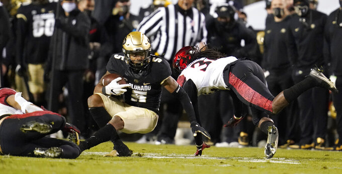 Colorado wide receiver La'Vontae Shenault, center, is stopped after catching a pass by San Diego State linebacker Michael Shawcroft, left, and safety Dwayne Johnson Jr. in the second half of an NCAA college football game Saturday, Nov. 28, 2020, in Boulder, Colo. (AP Photo/David Zalubowski)
