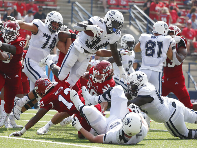 Connecticut running back Kevin Mensah (34) goes up for a short gain against Fresno State during the first half of an NCAA college football game in Fresno, Calif., Saturday, Aug. 28, 2021. (AP Photo/Gary Kazanjian)