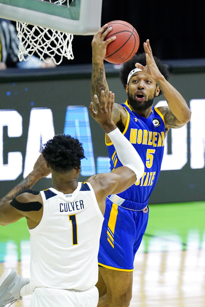 Morehead State's Skyelar Potter (5) shoots against West Virginia's Derek Culver (1) during the first half of a college basketball game in the first round of the NCAA tournament at Lucas Oil Stadium Friday, March 19, 2021, in Indianapolis. (AP Photo/Mark Humphrey)