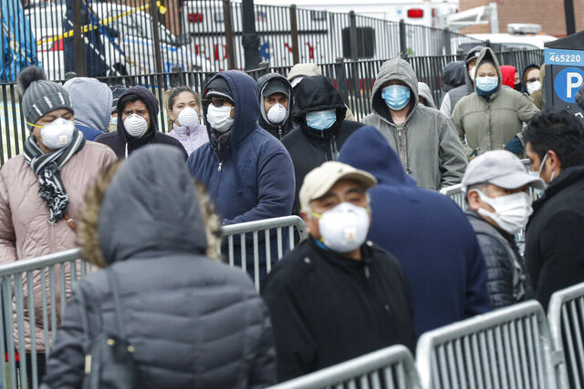 Patients wear personal protective equipment while maintaining social distancing as they wait in line for a COVID-19 test at Elmhurst Hospital Center, Wednesday, March 25, 2020, in New York. Gov. Andrew Cuomo sounded his most dire warning yet about the coronavirus pandemic Tuesday, saying the infection rate in New York is accelerating and the state could be as close as two weeks away from a crisis that sees 40,000 people in intensive care. Such a surge would overwhelm hospitals, which now have just 3,000 intensive care unit beds statewide. (AP Photo/John Minchillo)