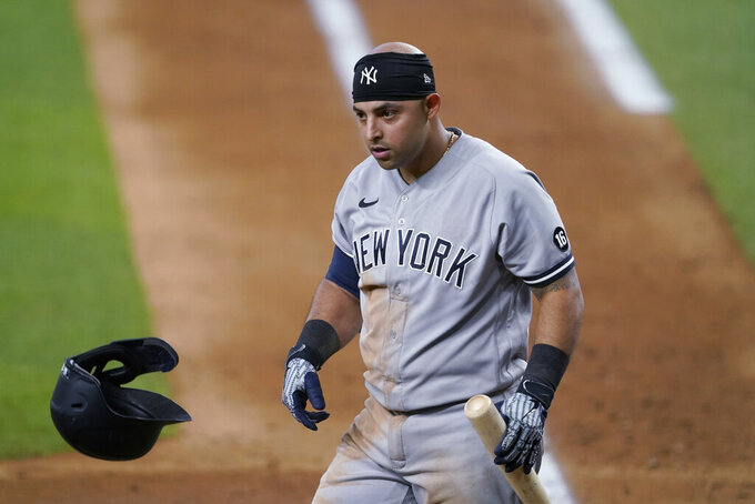 New York Yankees' Rougned Odor tosses his helmet and looks to the dugout after striking out during the seventh inning of the team's baseball game against the Texas Rangers in Arlington, Texas, Tuesday, May 18, 2021. (AP Photo/Tony Gutierrez)