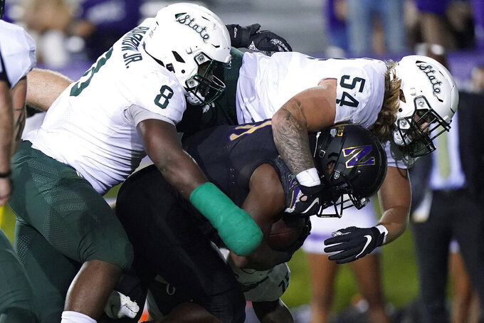 Michigan State defensive tackle Simeon Barrow (8) and defensive tackle Kyle King (54) tackle Northwestern running back Andrew Clair during the second half of an NCAA college football game in Evanston, Ill., Friday, Sept. 3, 2021. Michigan State won 38-21. (AP Photo/Nam Y. Huh)