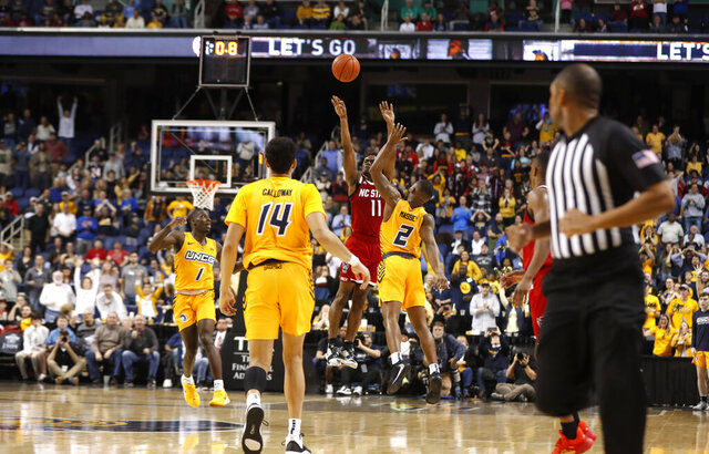 North Carolina State's Markell Johnson (11) makes a last-second basket as UNC Greensboro's Malik Massey (2) defends during an NCAA college basketball game in Greensboro, N.C., Sunday, Dec. 15, 2019. (Ethan Hyman/The News & Observer via AP)