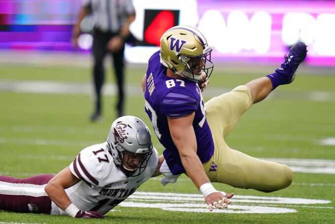 Washington's Cade Otton (87) is brought down by Montana's Robby Hauck in the first half of an NCAA college football game Saturday, Sept. 4, 2021, in Seattle. (AP Photo/Elaine Thompson)