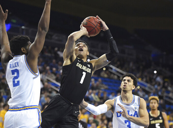 Colorado guard Tyler Bey shoots between UCLA forward Cody Riley, left, and guard Jules Bernard during the first half of an NCAA college basketball game Thursday, Jan. 30, 2020, in Los Angeles. (AP Photo/Michael Owen Baker)