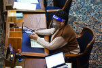 Rep. Phyllis Thede, D-Bettendorf, works at her desk during the opening day of the Iowa Legislature, Monday, Jan. 11, 2021, at the Statehouse in Des Moines, Iowa. (AP Photo/Charlie Neibergall)
