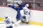 Vancouver Canucks' Josh Teves (34) checks Jack Rathbone (3) during NHL hockey team's training camp, Tuesday, Jan. 5, 2021 in Vancouver, British Columbia. (Darryl Dyck/The Canadian Press via AP)