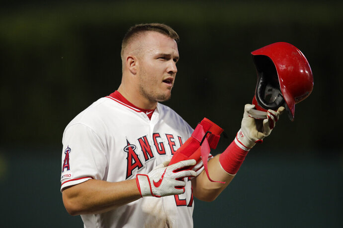 Los Angeles Angels' Mike Trout takes off his helmet after the first inning of a baseball game against the Milwaukee Brewers, Monday, April 8, 2019, in Anaheim, Calif. (AP Photo/Jae C. Hong)