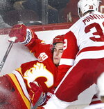 Calgary Flames defenseman Noah Hanifin (55) is knocked into the boards by Detroit Red Wings right wing Anthony Mantha (39) during second-period NHL hockey action in Calgary, Alberta, Thursday, Oct. 17, 2019.  (Larry MacDougal/The Canadian Press via AP)