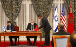 FILE - In this Dec. 22, 2020 file photo, Morocco and Israel sign agreements on direct flights, financial cooperation, visa waivers for diplomats and water technology cooperation at the guest house next to the royal palace in Rabat, Morocco. Two Israeli airlines launched their first commercial flights between Israel and Morocco on Sunday, July 25, 2021, less than a year after the countries officially normalized relations. (AP Photo/Abdeljalil Bounhar, File)
