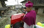 Catholic Bishop Ruben Dario Jaramillo Montoya sprinkles holy water as he travels on a fire truck through Buenaventura, Colombia, Saturday, July 13, 2019. Jaramillo traveled on a fire truck to some of Buenaventura's most crime-ridden neighborhoods on Saturday, sprinkling water that he had blessed in what he called an attempt to thwart drug trafficking gangs and other illegal groups. (AP Photo/Fernando Vergara)