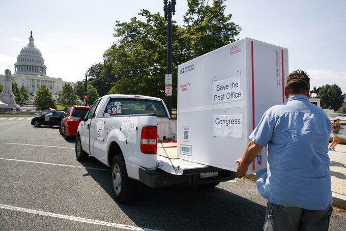 """Paul Falcon unloads a custom made """"Priority Mail"""" box that organizers said contained two million signed petitions from postal customers asking Congress to approve emergency funding for the Postal Service, Tuesday, June 23, 2020, on Capitol Hill in Washington. Postal Service employees and supporters are urging Congress to to invest $25 billion to help the public Postal Service """"weather the pandemic and the deep recession."""" (AP Photo/Jacquelyn Martin)"""