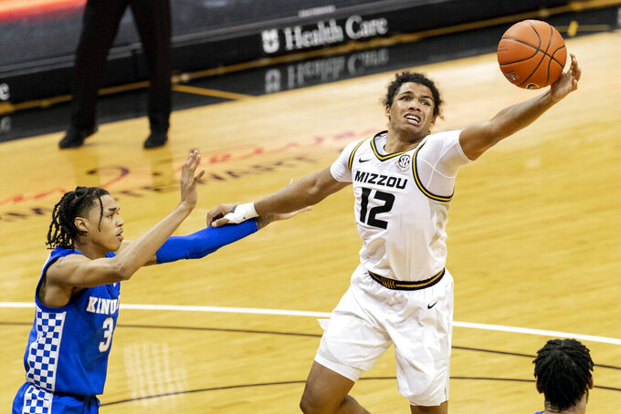 Missouri's Dru Smith, pulls down a rebound in front of Kentucky's Brandon Boston Jr., left, during the second half of an NCAA college basketball game Wednesday, Feb. 3, 2021, in Columbia, Mo. Missouri won 75-70. (AP Photo/L.G. Patterson)