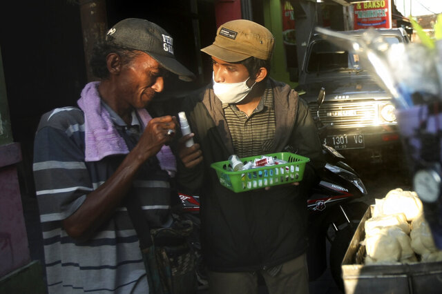 In this Thursday, March 26, 2020, photo, an activist distribute hand sanitizers and soaps to a street food vendor in Yogyakarta, Indonesia. A group of students from several universities in the central Java city has distributed soaps and hand sanitizers to informal daily workers whose incomes are affected by the coronavirus outbreak. (AP Photo/Fahmi Rosyidi)