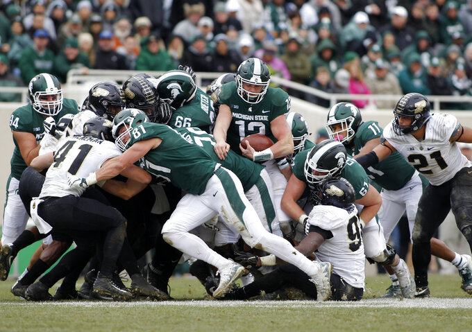 Michigan State quarterback Rocky Lombardi (12) emerges from the pile on a quarterback sneak for a first down against Purdue during the fourth quarter of an NCAA college football game, Saturday, Oct. 27, 2018, in East Lansing, Mich. Michigan State won 23-13. (AP Photo/Al Goldis)