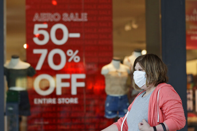 FILE - In this June 10, 2020 file photo, a woman walks past a store with sale signs displayed at Great Lakes Mall, in Mentor, Ohio. The Federal Reserve says economic activity has picked up in most regions of the country but still remains well below pre-pandemic levels with the country facing high levels of uncertainty. The Fed reported Wednesday, July 15 that its latest survey of economic conditions around the country found improvements in consumer spending and other areas but said the gains were from very low levels seen when widespread lockdowns push the country into a deep recession. (AP Photo/Tony Dejak, File)
