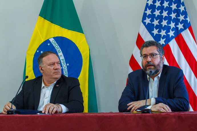 U.S. Secretary of State Mike Pompeo looks at Brazilian Foreign Minister Ernesto Araujo speaking during a press conference at the Boa Vista Air Base in Roraima, Brazil, Friday, Sept. 18, 2020. The stop in Brazil is part of Pompeo's three-day visit of his South American tour. (Bruno Mancinelle/Pool via AP)