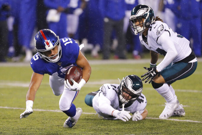 New York Giants wide receiver Golden Tate (15) falls with the ball in front of Philadelphia Eagles linebacker Nate Gerry (47) and Eagles cornerback Cre'von LeBlanc (34) in the first half of an NFL football game, Sunday, Dec. 29, 2019, in East Rutherford, N.J. (AP Photo/Seth Wenig)