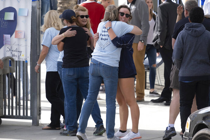 Saugus students hug as they arrive at Saugus High Tuesday, Nov. 19, 2019. Students were allowed back to collect their belongings left behind after the tragic shooting last Thursday. Classes will resume at the high school on Dec. 2.  (David Crane/The Orange County Register via AP)