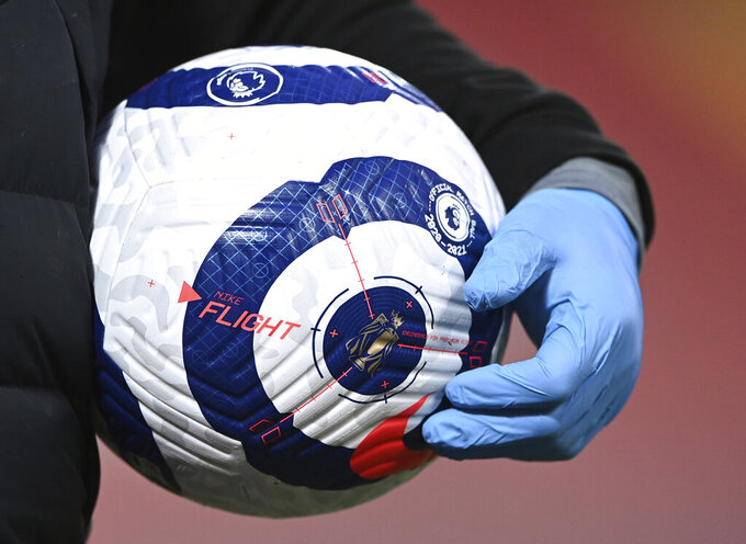 A member of the ground staff carries a ball wearing plastic gloves against the coronavirus ahead of the English Premier League soccer match between Liverpool and Everton at Anfield in Liverpool, England, Saturday, Feb. 20, 2021. (Lawrence Griffiths/ Pool via AP)