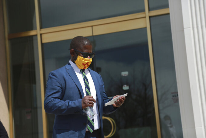FILE - In this April 5, 2021, file photo, New Mexico Education Secretary Ryan Stewart prepares to switch masks outside the state Capitol in Santa Fe, New Mexico. New Mexico education officials accepted a federal decision barring them from taxing millions in federal aid sent to school districts serving tribal areas and military bases. Stewart said Tuesday, June 15 that the state will not appeal the decision because it would likely lose. (AP Photo/Cedar Attanasio, File)