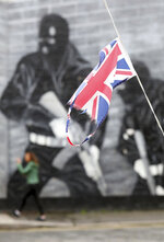 In this Tuesday, Oct. 15, 2019 photo a Union flag flutters in the shadow of a Loyalist mural from the Ulster Volunteer Force in East Belfast, Northern Ireland. (AP Photo/Peter Morrison)