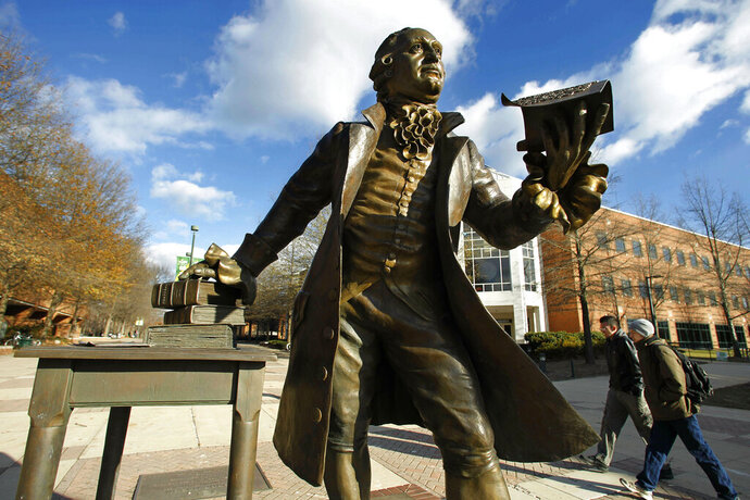 """FILE - In this Tuesday, Dec 14, 2010 file photo, a statue of George Mason stands in the heart of George Mason University's Fairfax campus in Fairfax, Va.  Newly released documents show that a $50 million gift to Virginia's largest public university was given specifically to """"promote the conservative principles of governance,"""" raising concerns from critics that that it compromises academic freedom. (AP Photo/Manuel Balce Ceneta, File)"""