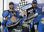 Kevin Harvick holds up his trophy after winning the first of two qualifying auto races for the NASCAR Daytona 500 at Daytona International Speedway, Thursday, Feb. 14, 2019, in Daytona Beach, Fla. (AP Photo/Terry Renna)