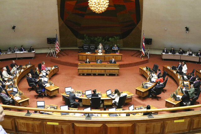 FILE -- This May 2, 2019 file photo shows lawmakers meet on the floor of the state House of Representatives at the Hawaii State Capitol in Honolulu. Cut spending, raise taxes, or perhaps both. Hawaii lawmakers face tough choices as they convene a new legislative session this week amid a pandemic that has pummeled tourism, the state's biggest industry, and depleted tax revenue. Lawmakers expect to spend time addressing how to spend federal funds allocated to help Hawaii test for the coronavirus, distribute vaccines, and bolster hospitals. They'll also consider how to help Hawaii's economy recover from the public health crisis. (AP Photo/Audrey McAvoy, File)