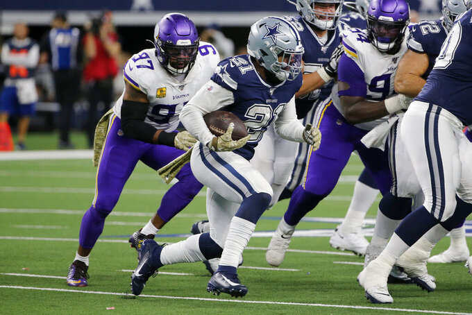 Dallas Cowboys running back Ezekiel Elliott (21) carries the ball as Minnesota Vikings' Everson Griffen (97) gives chase during the second half of an NFL football game in Arlington, Texas, Sunday, Nov. 10, 2019. (AP Photo/Michael Ainsworth)