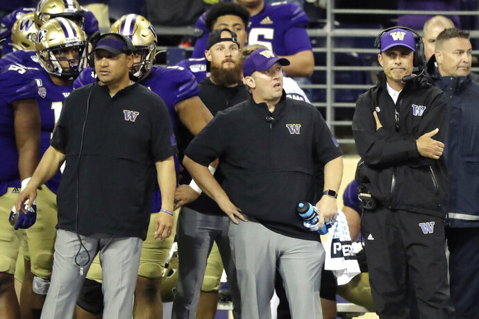 Washington head coach Chris Petersen, right, stands with other members of his staff late in the second half of an NCAA college football game in the early hours of Sunday, Sept. 8, 2019, in Seattle. California won 20-19. (AP Photo/Ted S. Warren)
