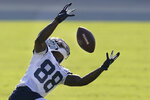 Dallas Cowboys wide receiver CeeDee Lamb (88) reaches for a pass during NFL football training camp in Frisco, Texas, Friday, Aug. 14, 2020. (AP Photo/LM Otero)