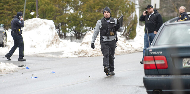 Police Detective Ryan Rawstron walks past bullet casings that litter the street in front of 21 Walnut Street in Lewiston, Maine early Saturday morning, Jan. 11, 2020, after a reported fight and shooting several hours earlier resulted in a standoff with the Maine State Police Tactical Team. (Russ Dillingham/Sun Journal via AP)