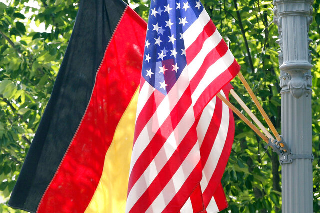 FILE - In this June 6, 2011 file photo, the German and U.S. flags fly on a lamp post in front of the White House in Washington ahead of German Chancellor Angela Merkel's visit. Defense officials say the U.S. will pull 12,000 troops from Germany, bringing 6,400 forces home and shifting 5,600 to other countries in Europe, including Italy and Belgium. The plan will cost billions of dollars and take years to complete.  (AP Photo/Charles Dharapak)