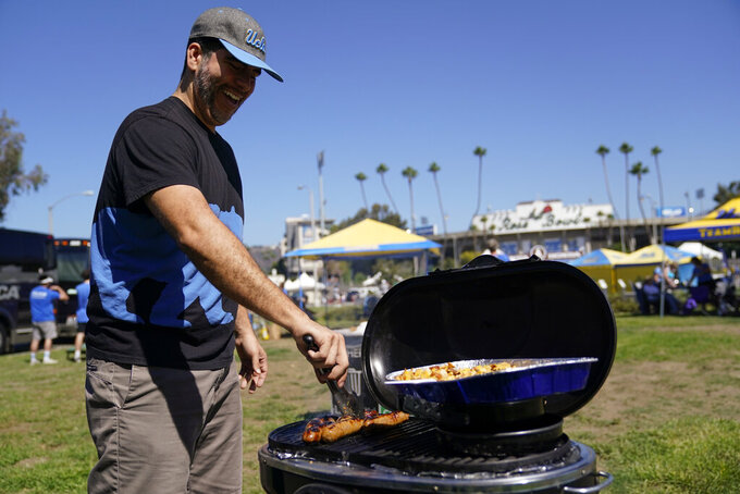 Hector Amezquita grills sausages while tailgating outside of the Rose Bowl before an NCAA college football game between the Hawaii Warriors and the UCLA Bruins Saturday, Aug. 28, 2021, in Pasadena, Calif. Colleges across the country are cautiously optimistic that pregame tailgating will largely return to normal even since the emergence of the delta variant of the coronavirus. (AP Photo/Ashley Landis)