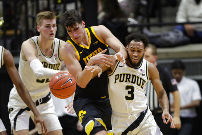Iowa center Luka Garza (55) goes over Purdue guard Jahaad Proctor (3) for a loose ball during the second half of an NCAA college basketball game in West Lafayette, Ind., Wednesday, Feb. 5, 2020. Purdue defeated Iowa 104-68. (AP Photo/Michael Conroy)