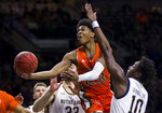 Miami's Kameron McGusty (23) goes up for a shot between Notre Dame's John Mooney (33) and Temple 'T.J.' Gibbs (10) during the first half of an NCAA college basketball game Sunday, Feb. 23, 2020, in South Bend, Ind. (AP Photo/Robert Franklin)