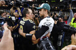 New Orleans Saints quarterback Drew Brees (9) speaks with Philadelphia Eagles quarterback Nick Foles after an NFL divisional playoff football game in New Orleans, Sunday, Jan. 13, 2019. The Saints won 20-14 to advance to the NFC Championship. (AP Photo/Bill Feig)