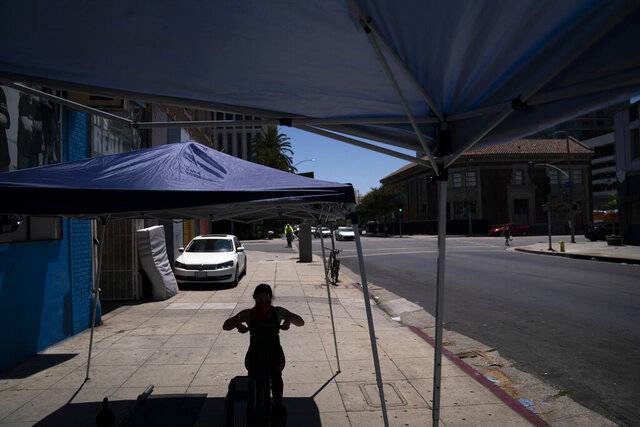 FILE - In this Aug. 7, 2020, file photo, a woman works out at an outdoor gym in Los Angeles. Gov. Gavin Newsom said Wednesday, Aug. 12, 2020, that California was turning the corner in its fight against the coronavirus pandemic, citing a significantly lower number of confirmed new cases as the state begins to clear backlogged cases from a data failure. (AP Photo/Jae C. Hong, File)