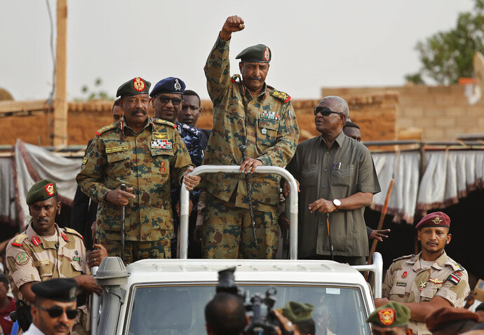 FILE - In this Saturday, June 29, 2019, file photo, Sudanese Gen. Abdel-Fattah Burhan, head of the military council, waves to his supporters upon his arrival to attend a military-backed rally in Omdurman district, west of Khartoum, Sudan. The power-sharing agreement reached between Sudan's military and pro-democracy protesters last week came after the United States and its Arab allies applied intense pressure on both sides amid fears a prolonged crisis could tip the country into civil war, activists and officials said. (AP Photo/Hussein Malla)