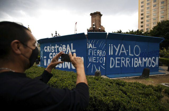 A pedestrian takes a photo of graffiti that reads in Spanish