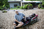 In this Wednesday, June 12, 2019, photo, Eric Luther poses for a picture at his house in Carmel, N.Y. Luther's yard was covered in gravel or wood chips, by the Environmental Protection Agency, as a bulwark against high levels of arsenic in the soil. (AP Photo/Seth Wenig)
