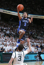 Duke's Tre Jones, top, goes over Michigan State's Foster Loyer for a layup during the first half of an NCAA college basketball game, Tuesday, Dec. 3, 2019, in East Lansing, Mich. (AP Photo/Al Goldis)