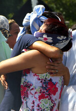 Women who cover their faces so as not to be identifiable by the press and police embrace outside Anisio Jobim Prison Complex after a deadly riot erupted among inmates in Manaus in the northern state of Amazonas, Brazil, Sunday, May 26, 2019. A statement from the state prison secretary says prisoners began fighting among themselves around noon Sunday, and security reinforcements were rushed to complex. (AP Photo/Edmar Barros)