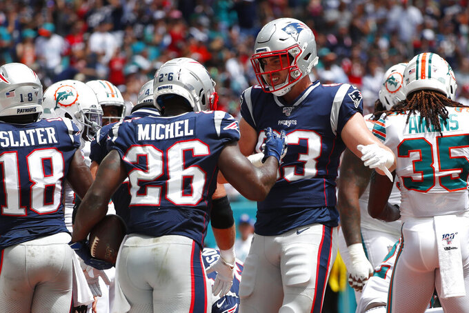 New England Patriots tight end Matt LaCosse (83) congratulates running back Sony Michel (26) after Michel scored a touchdown, during the first half at an NFL football game against the Miami Dolphins, Sunday, Sept. 15, 2019, in Miami Gardens, Fla. (AP Photo/Wilfredo Lee)