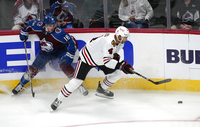Chicago Blackhawks defenseman Seth Jones, right, fights for control of the puck with Colorado Avalanche center Alex Newhook in the first period of an NHL hockey game Wednesday, Oct. 13, 2021, in Denver. (AP Photo/David Zalubowski)
