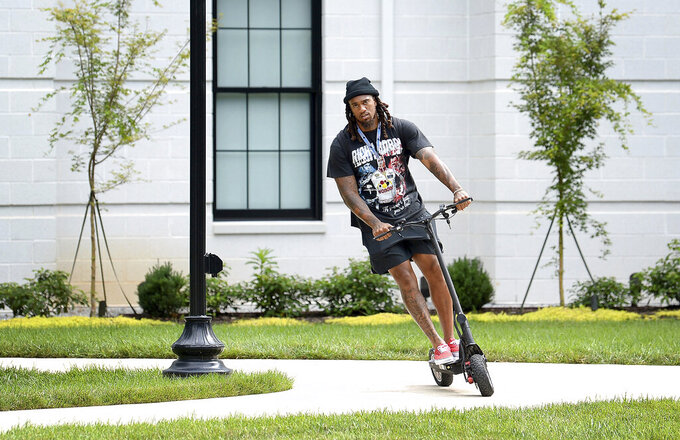 Carolina Panthers linebacker Shaq Thompson rides a scooter outside the team's dormitory at NFL football training camp, Tuesday, July 27, 2021, at Wofford College in Spartanburg, S.C. (Jeff Siner/The Charlotte Observer via AP)
