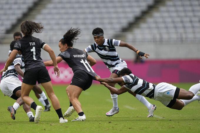 Fiji's Rusila Nagasau, right, tries to stop New Zealand's Portia Woodman, center, in their women's rugby sevens semifinal match at the 2020 Summer Olympics, Saturday, July 31, 2021 in Tokyo, Japan. (AP Photo/Shuji Kajiyama)