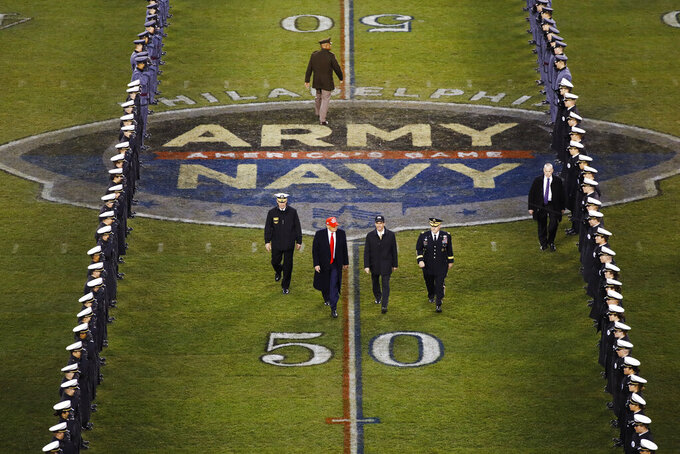 FILE - President Donald Trump and Secretary of Defense Mark Esper cross the field after the first half of an NCAA college football game between Army and Navy in Philadelphia, in this Saturday, Dec. 14, 2019, in file photo. Bump Army-Navy or go head-to-head with NFL? That's the choice facing those in charge with expanding the College Football Playoff if they want to take the format from four to 12 teams. (AP Photo/Matt Rourke, File)